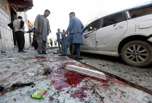 Varios hombres inspeccionan un lugar cercano a la explosión registrada en un centro de votantes de la capital afgana.