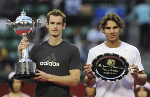 El tenista español Rafael Nadal (dcha) sostiene su bandeja de plata tras perder la final del Torneo de Tokio contra el británico Andy Murray (izda).
