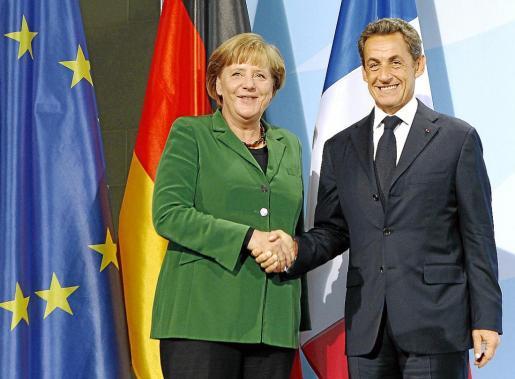La canciller alemana y el presidente francés se estrechan la mano tras el encuentro.