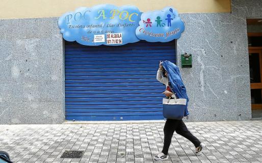 Una mujer pasa caminando junto a la guardería de Palma donde se produjeron los malos tratos.