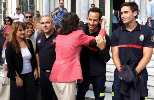 La consejera de Justicia de la Junta de Andalucía, Rosa Aguilar, abraza a Julio Latorre ante la presencia de Manuel Blanco (2i) y José Enrique Rodríguez (d), los otros dos bomberos de la ONG Proem-Aid, antes del juicio.