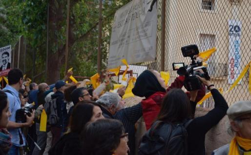 Varios manifestantes cuelgan lazos amarillos por la libertad de los políticos presos en un centro.