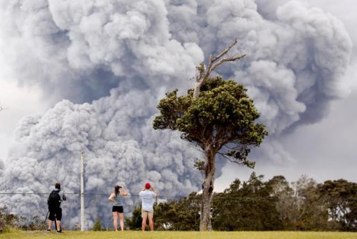 Un grupo de personas observando la nube de cenizas del volcán Kilauea.