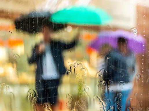 Varias personas se protegen de la lluvia caída el domingo en Mallorca.