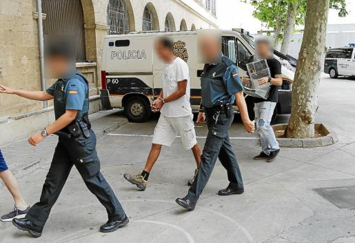 El detenido, entre dos guardias civiles, a su llegada ayer a los juzgados.