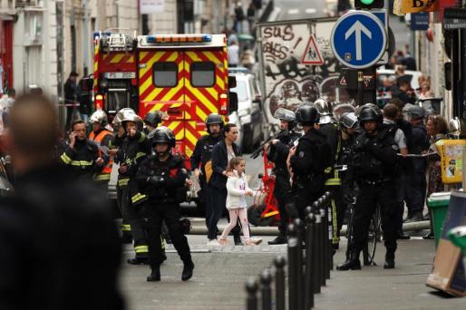 Una mujer y una niña son evacuadas por las fuerzas policiales durante una supuesta toma de rehenes en la Rue des Petites Ecuries, en París.