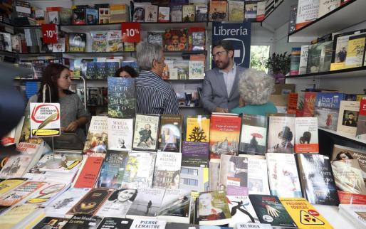 El ministro de Cultura y Deportes, Màxim Huerta (d), en la caseta de la editorial donde firmó libros durante su visita la Feria del Libro en el madrileño parque de El Retiro.