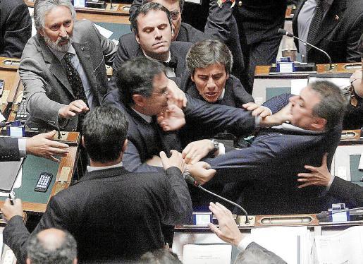LA156 ROMA (ITALIA) 26/10/2011 .- El diputado Claudio Barbaro, del partido Futuro e Liberta (centro a la izq) y el diputado de la Liga Norte, Fabio Rainieri (der) pelean después de que el diputado de la Liga Norte, Marco Reguzzoni pidiera la renuncia al presidente de la Cámara, Gianfranco Fini, hoy 26 de octubre de 2011 en el Palacio de Montecitorio en Roma, Italia. La sesión de cámara fue suspendida después de la reyerta entre los diputados, que se enfrentaron por los planes del gobierno de modificar la ed