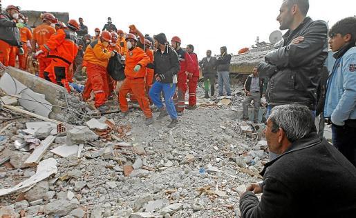 Miembros de los equipos de rescate transportan el cuerpo de una persona que fue encontrado entre los escombros.