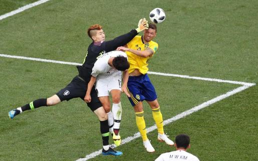 El sueco Marcus Berg intenta rematar ante la oposición del portero coreano Jo Hyeon-woo.