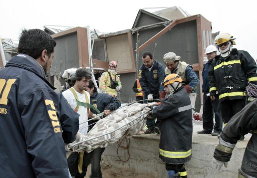 Rescatistas chilenos trasladan el cuerpo de un hombre que fue encontrado ayer, domingo 28 de febrero de 2010, en un edificio en Concepción (Chile).