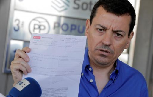 El militante del Partido Popular José Luis Bayo muestra el recibo de su pago de la cuota del partido durante la rueda de prensa ofrecida ante la sede del PPCV en Valencia para explicar las razones de la suspensión de su candidatura a la presidencia del PP.