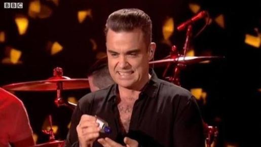 Robbie Williams se limpia las manos tras tocar a unos fans.