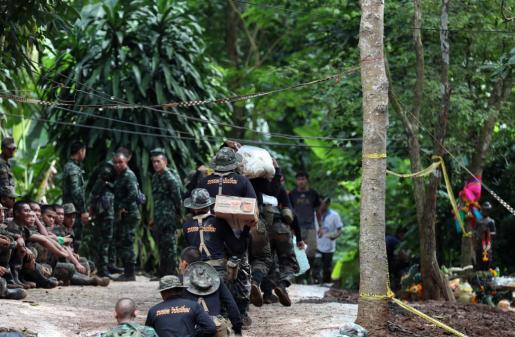 Varios soldado tailandeses llevan provisiones mientras continúan las labores de rescate de los doce niños y su monitor atrapados en una cueva parcialmente inundada en el parque de Khun Nam Nang Non, en la provincia de Chiang Rai (Tailandia).