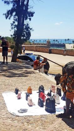 Venta ambulante ante la presencia de un coche de la Policía Local de Palma.