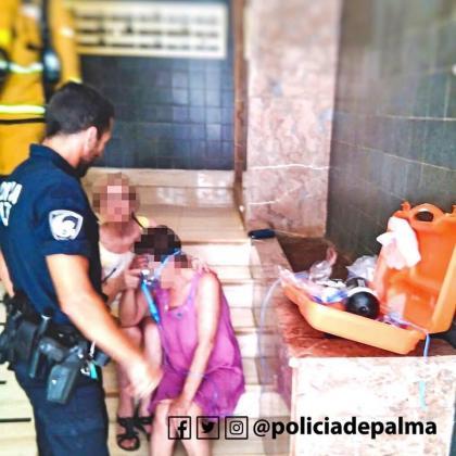 Un agente de la Policía de Palma atiende a una mujer afectada por el incendio en la calle Manacor.