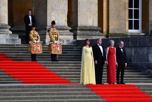 La primera dama estadounidense, Melania Trump; el presidente de EE.UU., Donald Trump; la primera ministra británica, Theresa May, y su esposo, Philip, permanecen juntos en los escalones de la Gran Corte mientras las bandas de guardia escocesas, irlandesas y galesas dan la bienvenida ceremonial a Trump.
