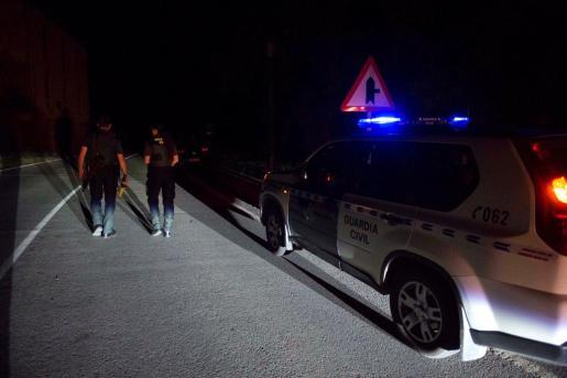 Dos agentes de la Guardia Civil cortan la carretera que da acceso al lugar en el que un hombre se ha atrincherado en una casa de Turieno, en el municipio cántabro de Camaleño, desde la que ha realizado varios disparos a la Guardia Civil.