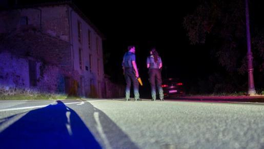 Dos agentes de la Guardia Civil cortan la carretera que da acceso al lugar en el que un hombre se atrincheró desde la noche.