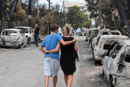 Una pareja camina junto a varios vehículos calcinados en una zona afectada por los incendios en Argyra Akti, en Mati (Grecia).