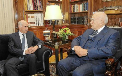 El presidente griego, Carolos Papoulias (d), y el primer ministro, Yorgos Papandréu, durante la reunión que mantuvieron ayer.