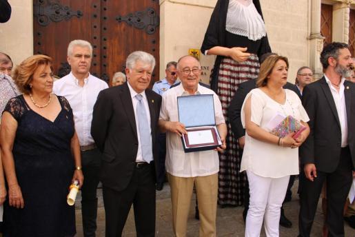 Tomeu Català junto al alcalde de Alcúdia, enseña la placa al público.