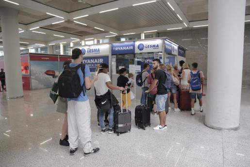 Numerosos pasajeros hacen cola en el aeropuerto de Palma junto a la oficina de Ryanair.