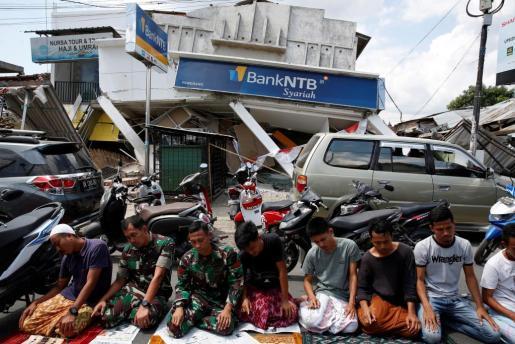 Residentes y soldados rezan frente a un edificio derruido. Han resultado destruidos o dañados 67.857 casas, 468 colegios, 6 puentes, 50 oratorios, 20 oficinas, 15 mezquitas y 13 centros sanitarios.