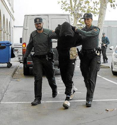 Dos guardias civiles custodian al detenido.