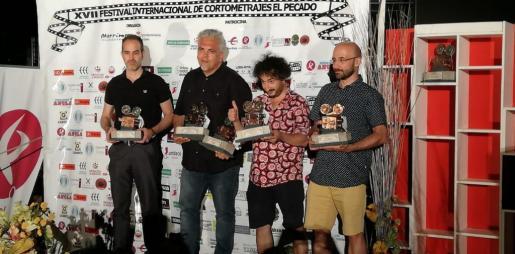 El cineasta mallorquín Toni Bestard, segundo por la izquierda, sostiene su estatuilla y la de Marcos Cabotà, quien no acudió a la ceremonia de entrega de premios del XVII certamen de cine 'El Pecado', de Llerena.