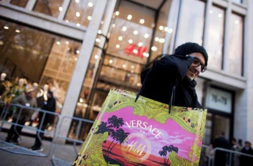 Un hombre muestra su bolsa al salir de una tienda H&M tras el lanzamiento de la colección de Versace para H&M, hoy jueves 17 de noviembre de 2011 en Duesseldorf.