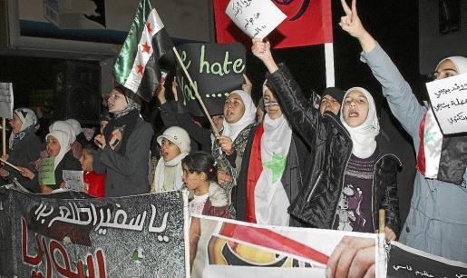 Sirios residentes en Jordania muestran pancartas contra Al Asad ante la Embajada siria en Amán.