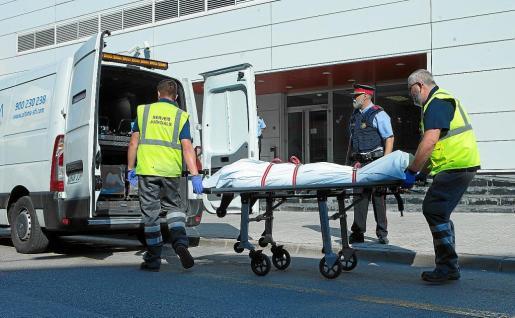 Miembros del servicio judicial retiran el cadáver del hombre que fue abatido este lunes al intentar acceder a la comisaría de los Mossos de Cornellà con un cuchillo en la mano y al grito de 'Alá es grande'.