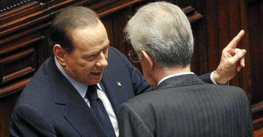 Silvio Berlusconi se dirige con un gesto aparentemente amenazante a su sucesor en el cargo de primer ministro