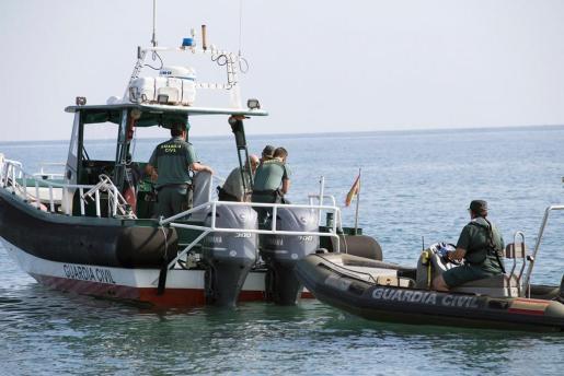 Agentes del Servicio Especial de Actividades Subacuáticas de la Guardia Civil tras recuperar el cadáver de un joven en una playa de Salobreña (Granada), a unos diez metros de la orilla