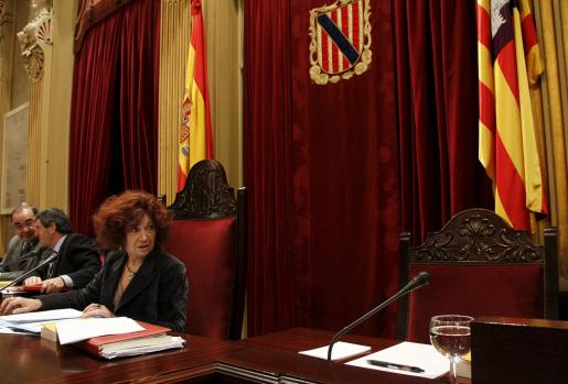 La presidenta del Parlament, Aina Rado, mira la silla que ocupaba hasta la dimisión de Maria Antònia Munar.