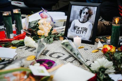 Fotografía de archivo muestra una foto del difunto músico británico John Lennon junto a velas y flores durante el 36 aniversario de su muerte, en el monumento Strawberry Fields, en Central Park, en Nueva York.