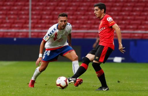 Fran Gámez controla en esférico ante la atenta mirada de Varela.