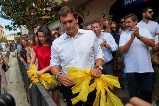El presidente de Cs y su líder en Cataluña, Albert Rivera (d) e Inés Arrimadas (i) , retiran lazos amarillos durante el recorrido que hicieron junto a cargos y afiliados del partido por la localidad barcelonesa de Alella.