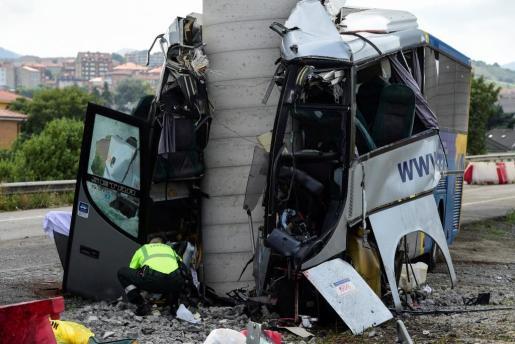Un guardia civil examina el autocar tras el choque.