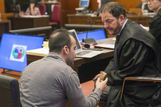 El presunto asesino de una bebé en Vitoria a la que lanzó por una ventana, Daniel M. (i), iz.,habla con su abogado, Martín Martínez.