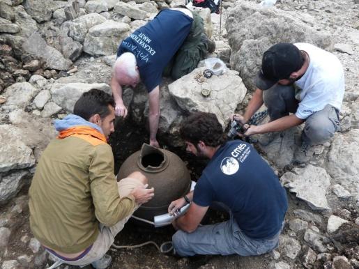 Arqueólogos y voluntarios sacan una gran vasija, que se conservó casi intacta tras el incendio que destruyó Almallutx en el siglo XIII, de una de las viviendas del yacimiento.