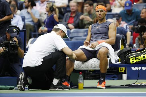 El mallorquín Rafael Nadal es atendido de sus molestias en la rodilla.