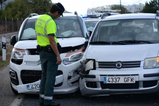 Un guardia civil observando dos de los vehículos implicados en el accidente.