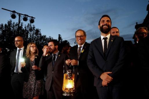 El presidente de la Generalitat Quim Torra (2d) y el presidente del Parlament Roger Torrent (d), acompañados por con los consellers Miquel Buch (i) Elsa Artadi (2i) y Pere Aragones (3i), con un farolillo con la Llama del Canigó durante una marcha por la libertad.