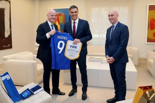 Pedro Sánchez (c), durante el encuentro que ha mantenido con el presidente de la Federación Española de Fútbol, Luis Rubiales (d), y el presidente de la FIFA, Gianni Infantino (i), hoy en el Palacio de la Moncloa.