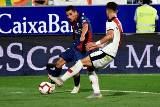 El centrocampista francés del Huesca, Serdar Gurler, golpea el balón ante el jugador del Rayo, Alex Moreno, durante el encuentro correspondiente a la tercera jornada de primera división disputado esta noche en el estadio El Alcoraz.