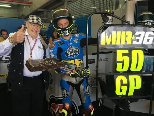 Joan Mir posa junto a un cartel conmemorativo de su 50 Gran Premio y con el jefe de su equipo.