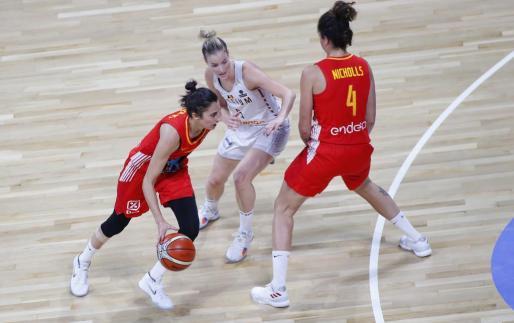 Alba Torrens conduce el balón ante un bloqueo de Laura Nicholls.