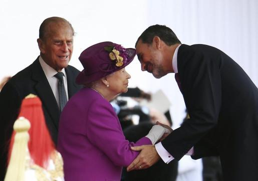 El rey Felipe VI de España, en presencia del duque Felipe de Edimburgo, besa a la reina Isabel II de Inglaterra.